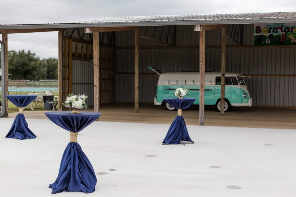 cocktail tables with navy table cloths and gold accents in front of turquoise van